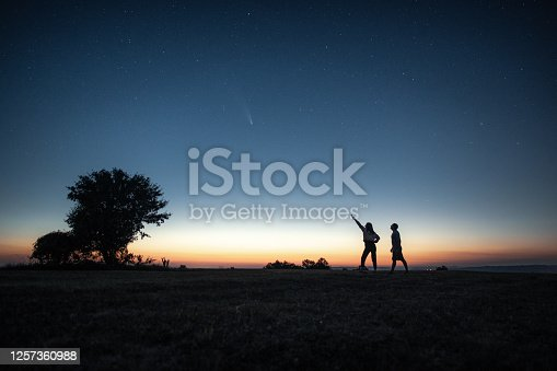 Silhouette of a young couple watching the Neowise comet  under the bright night sky after sunset