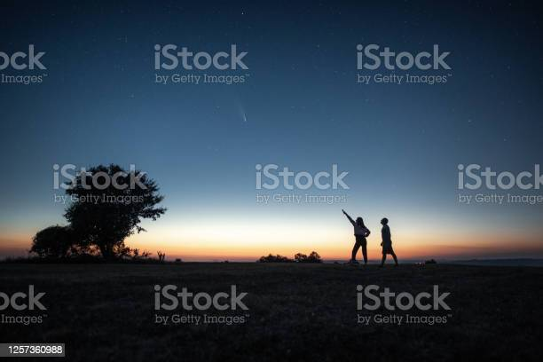 Photo of Young couple watching the Neowise comet under the bright night sky