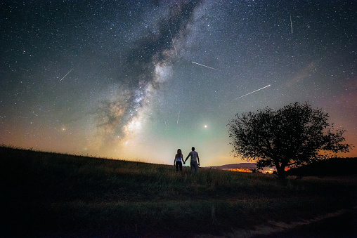 Young man and woman under the bright night sky watching the milky way and Perseid meteor shower
