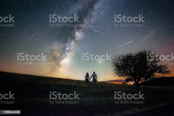 Photo of Young couple watching the Perseid meteor shower and the Milky way