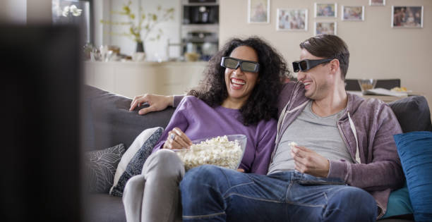 Young couple watching TV with 3D glasses stock photo