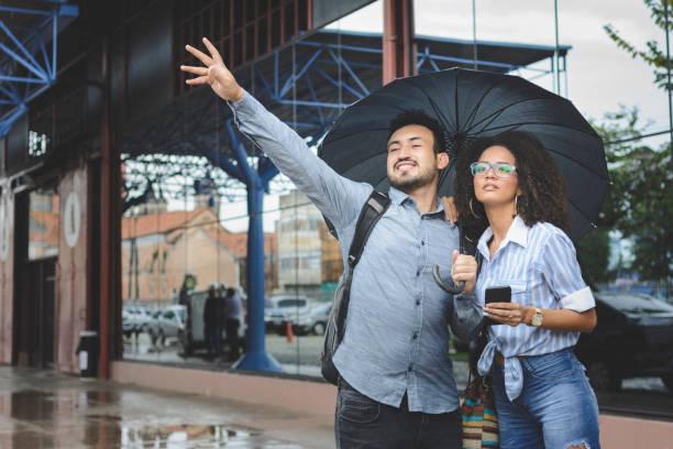 jeunes couples agitant pour le taxi qu'ils attendent pour un jour pluvieux - homme faire coucou voiture photos et images de collection