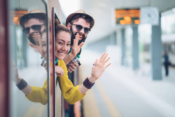 Young couple waving from the train window stock photo
