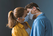 istock Young couple wearing a protective face mask and kissing 1209865909