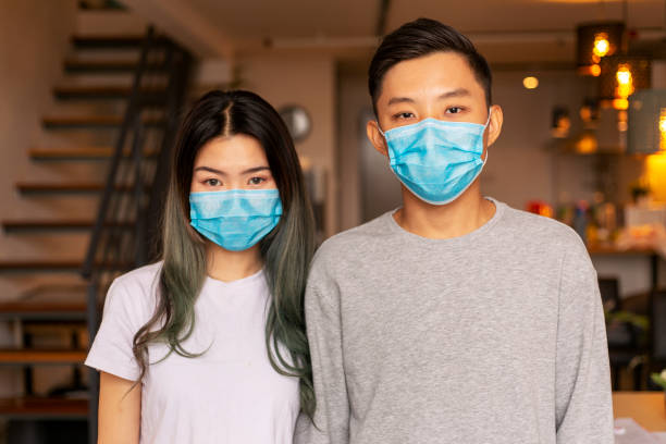 young couple wearing a protective face mask at home - trap house stock pictures, royalty-free photos & images
