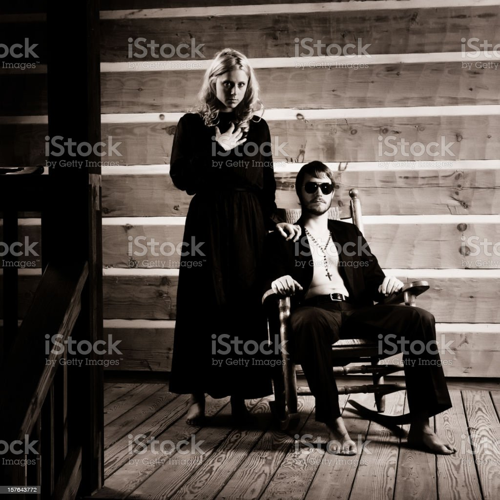 young couple wearing black clothes in their cabin porch stock photo