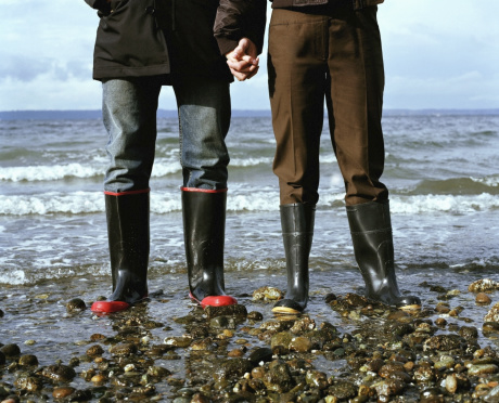 Young couple wearing galoshes, standing in surf, low section