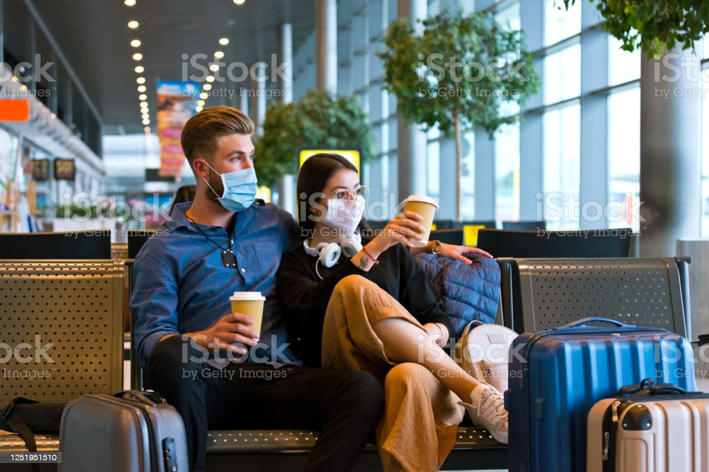 Young couple wearing N95 face masks waiting in airport area Young woman and man traveling by plane during COVID 19, wearing N95 face masks, sitting on bench with take away coffee in airport waiting area. Adult Stock Photo