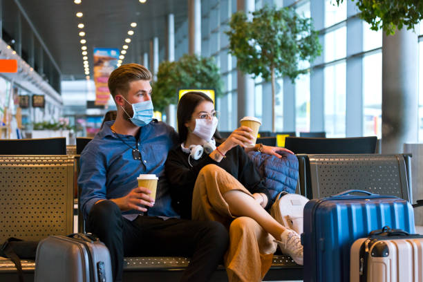 Young couple wearing N95 face masks waiting in airport area stock photo