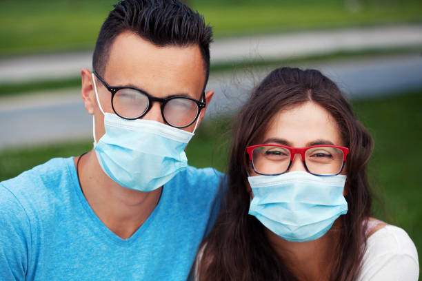 Young couple wearing protective face masks with eyeglasses stock photo