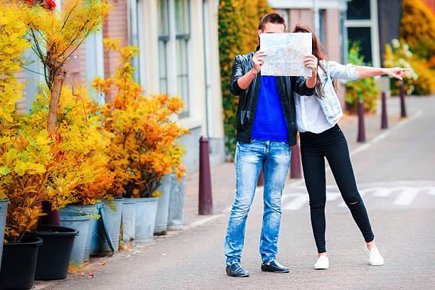 junges paar mit karte im freien - hochzeitsreise amsterdam stock-fotos und bilder