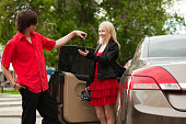 Young man is giving car key to his girlfriend.
