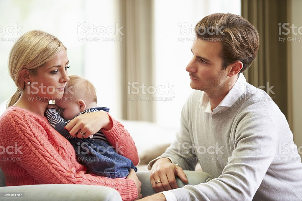 Young couple with baby looking sad stock photo