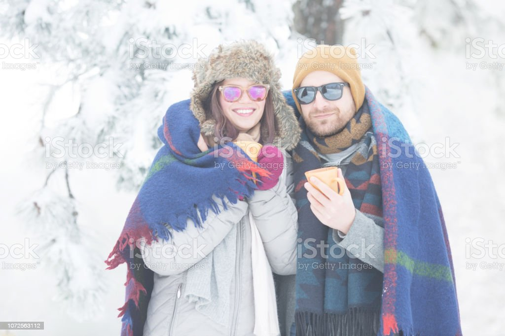 Young couple with blanket in winter outdoors stock photo