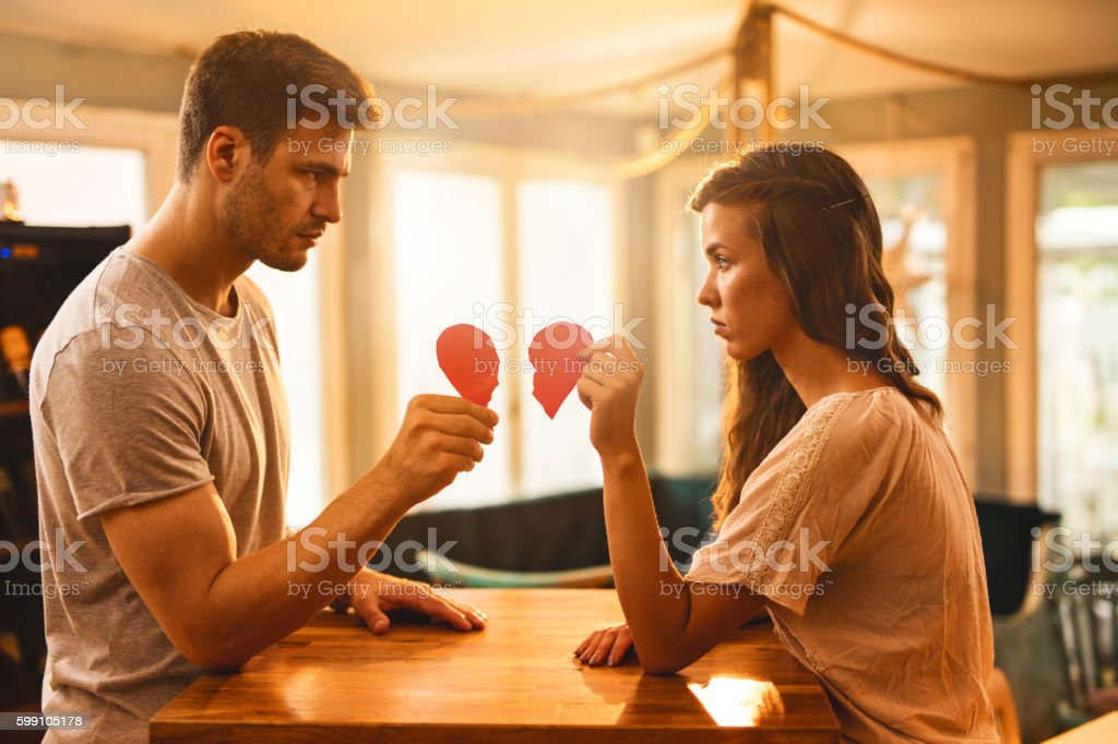 Young couple with broken heart shape looking at each other. stock photo