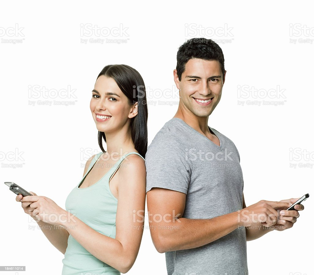 Young couple with cell phones on white background royalty-free stock photo