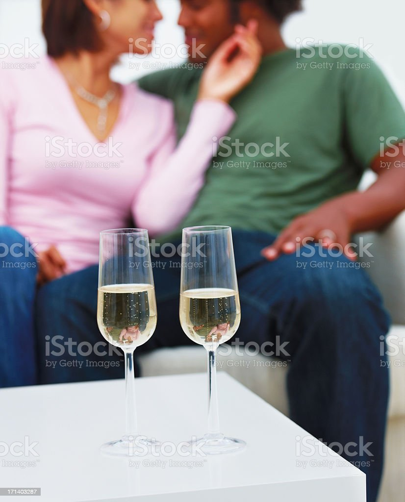 Young couple with champagne glasses in foreground royalty-free stock photo