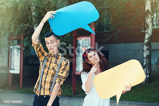 638013502istockphoto Young couple with chat bubbles 1002190000