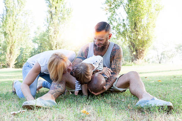 young couple with child having fun at the park - hipster mädchen tattoos stock-fotos und bilder