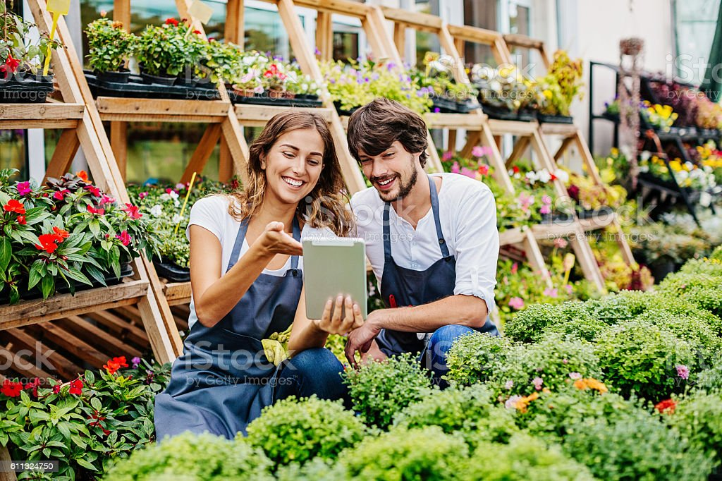 Young couple with digital tablet in garden center stock photo