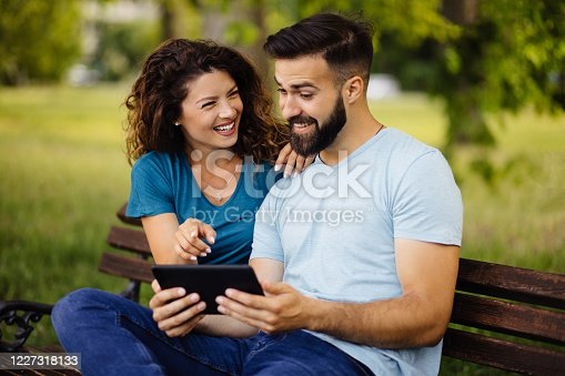 Young couple with digital tablet surfing the net in the park