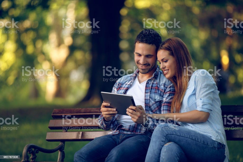 Young couple with digital tablet surfing the net - Foto stock royalty-free di Abbracciare una persona