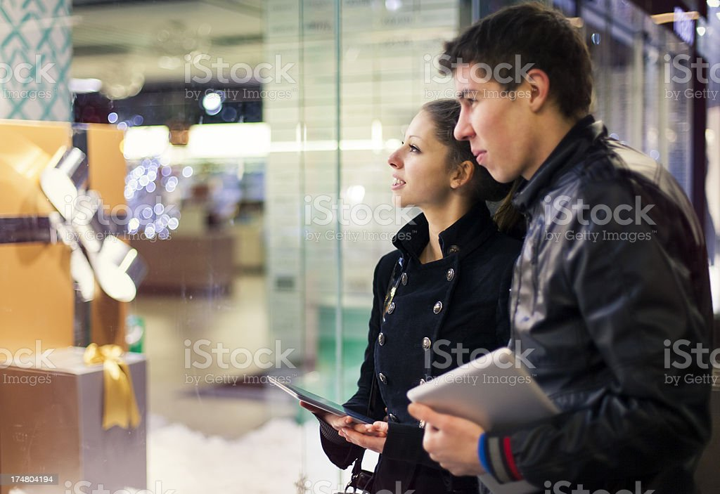 Young couple with digital tablets looking at store window royalty-free stock photo