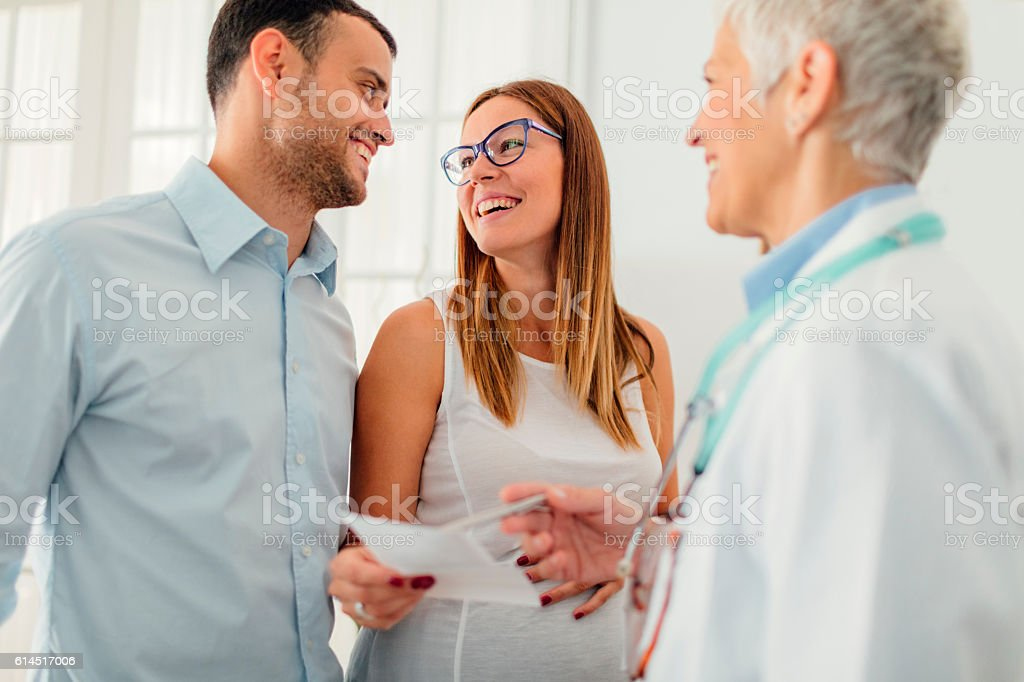 Young Couple with Doctor In A Consultation. stock photo