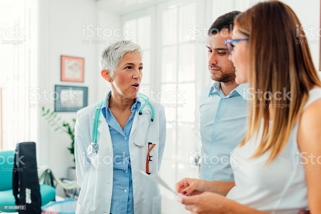 Young Couple with Doctor In A Consultation stock photo
