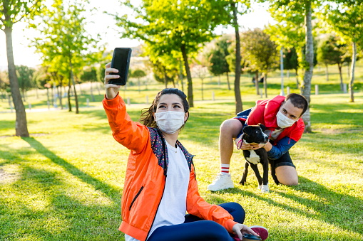 Young couple and dog sticking out tongues for a selfie at the park.