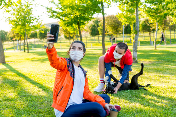 Young couple with dog in the park Young couple and dog sticking out tongues for a selfie at the park. cute teen couple stock pictures, royalty-free photos & images