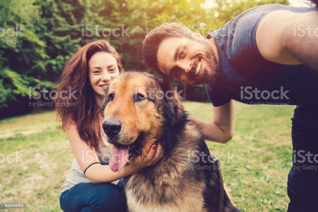 Jovem casal com cachorro no parque - foto de acervo