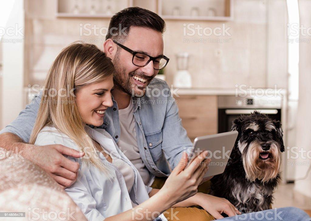 Junges Paar mit Hund Blick auf tablet – Foto