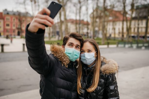 Young couple with face masks making a selfie stock photo