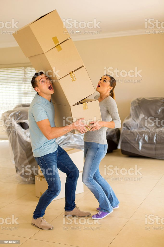 young couple with falling stack of boxes stock photo