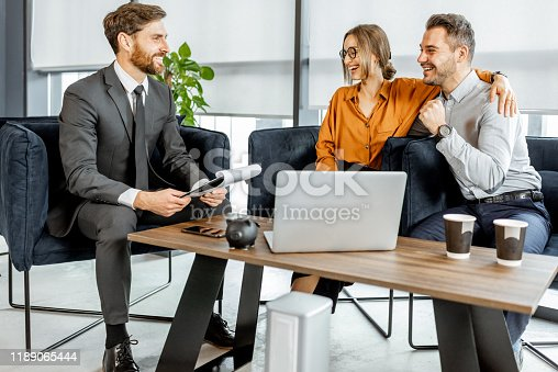 1178695243 istock photo Young couple with financial advisor at the office 1189065444