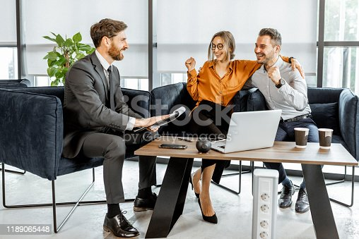 1178695243 istock photo Young couple with financial advisor at the office 1189065448