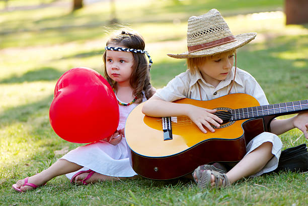 Young couple with guitar on grass in park stock photo