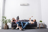 istock young couple with hand fan and newspaper suffering from heat at home with broken air conditioner 1256098103