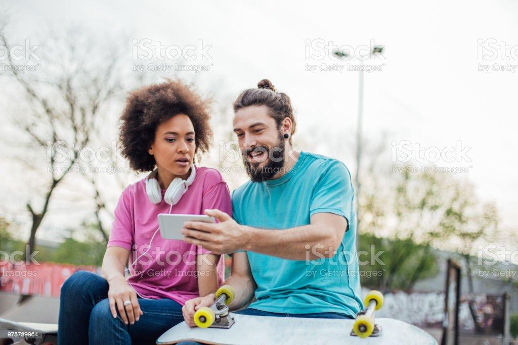 Junge Paar mit Kopfhörer und skateboard-Blick auf Handy - Lizenzfrei Afro-Amerikanischer Herkunft Stock-Foto