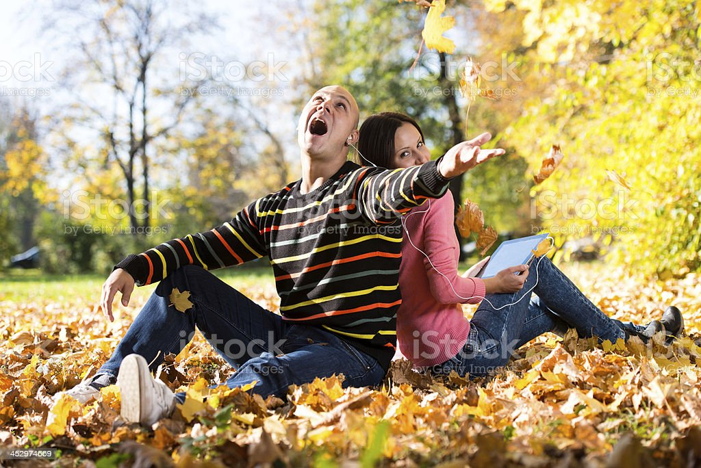Young Couple With Headphones And Throwing Fall Leaves royalty-free stock photo