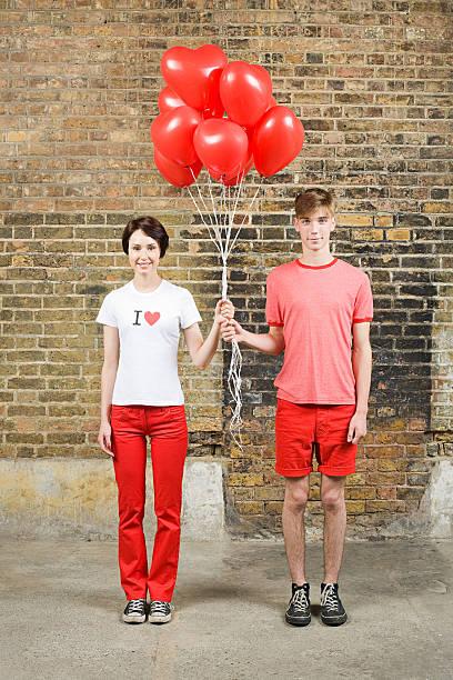 junges paar mit herzförmigen ballons - ballonhose stock-fotos und bilder