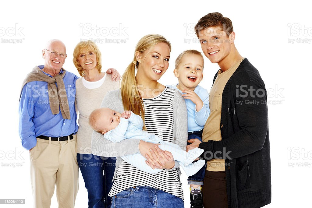 Young couple with kids and grandparents in background royalty-free stock photo