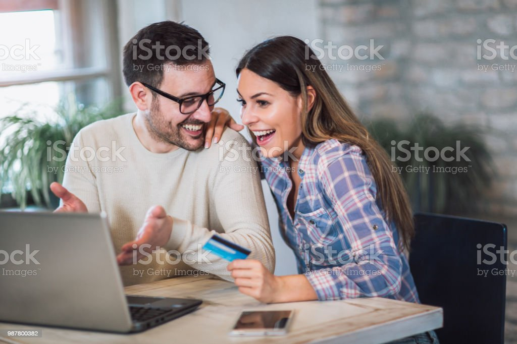 Young couple with Laptop Computer and Credit Card buying online stock photo