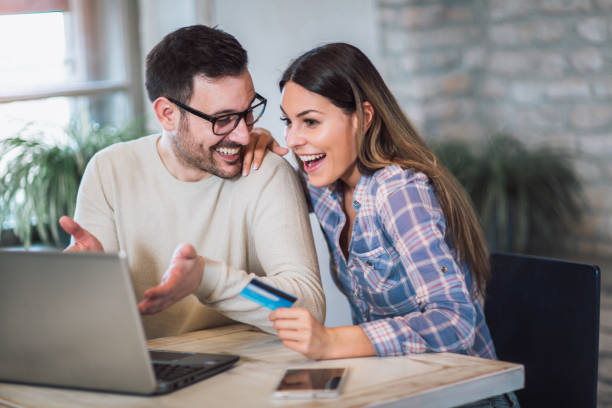 young couple with laptop computer and credit card buying online - online shopping zdjęcia i obrazy z banku zdjęć