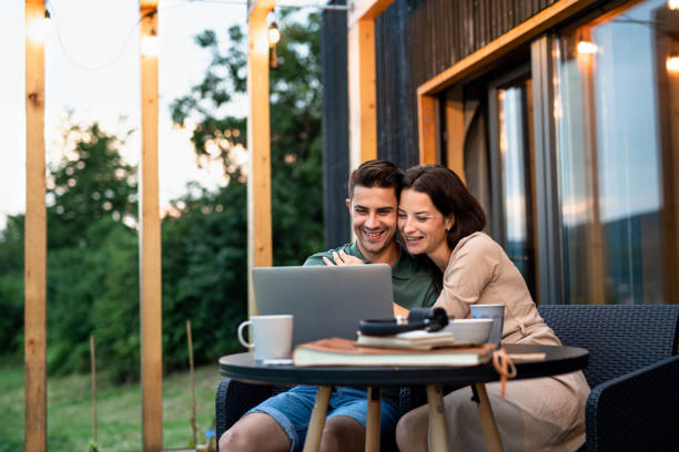 Young couple with laptop outdoors, weekend away in container house in countryside. stock photo