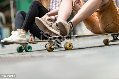 Young couple skateboard through the streets.