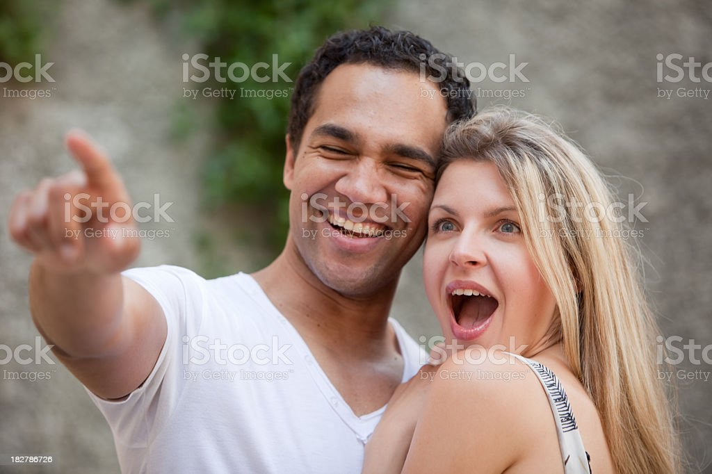 Young couple with man pointing and surprised woman stock photo