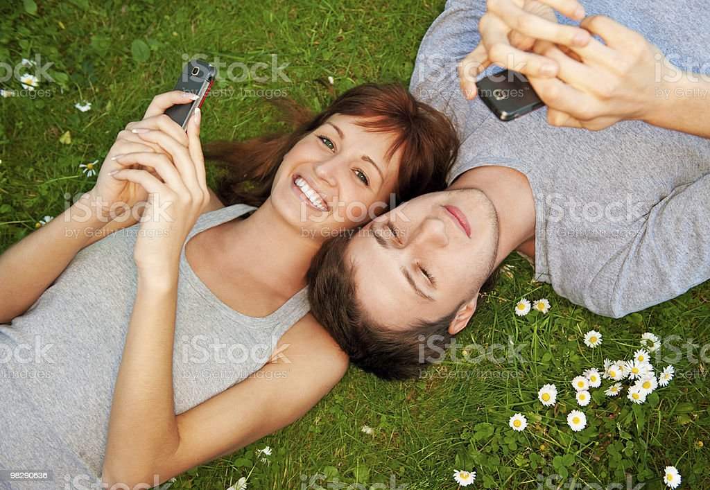 Young couple with mobile phones outdoors royalty-free stock photo