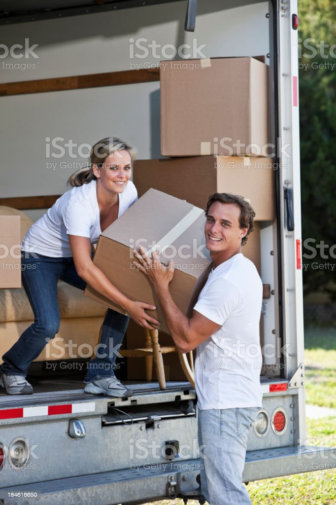 Young couple with moving van in driveway lifting boxes royalty-free stock photo